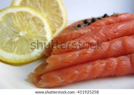 red fish on a white plate with lemon