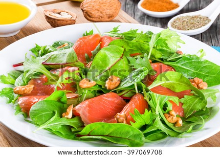 Red fish salad with mixed lettuce leaves on a white dish on a cutting board with olive oil and spice, close-up, top view - stock photo