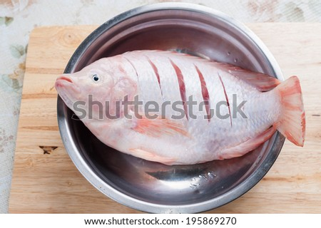 Red fish (Tilapia nilotica) on wood chopping board in kitchen. - stock photo