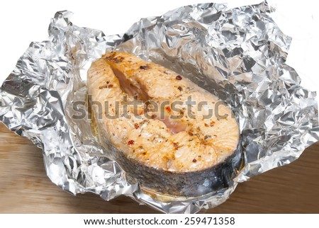 red fish with spice in foil on table - stock photo
