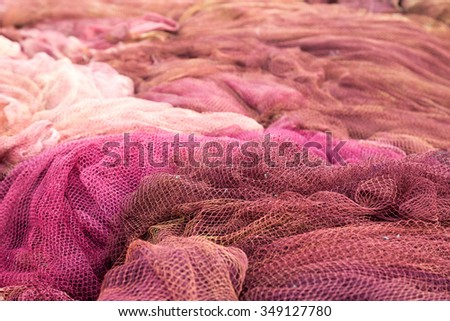 Red fishing nets drying on the port - stock photo