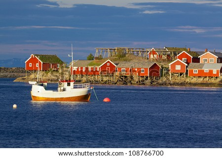 Red fishing rorbu huts and fishing boat in town of Reine on Lofoten islands - stock photo