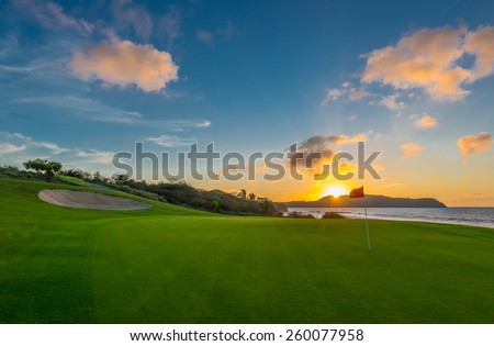 Red flag and sand bunker at the beautiful golf course at the ocean side at sunset, sunrise time. - stock photo