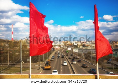 Red flag as a symbol of the holiday on the background of the industrial city with the transport, buildings and roads
