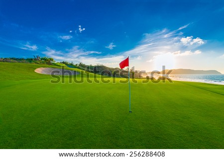 Red flag at the beautiful golf course at the ocean side at sunset, sunrise time. - stock photo