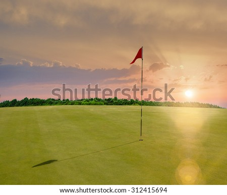 Red flag in a golf course during sunset - stock photo