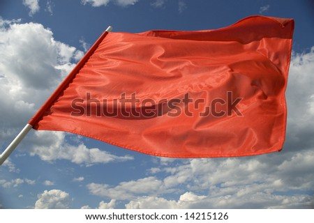 Red flag on a background of the dark blue sky with clouds.