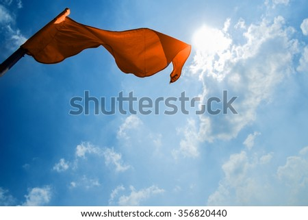 Red flag on a background of the dark blue sky with clouds. - stock photo