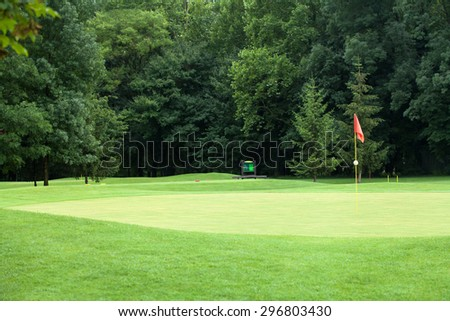 Red flag on a golf course, focus on the flag - stock photo