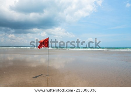 Red flag on beach with no swimming notes. Season of storms and strong currents. - stock photo
