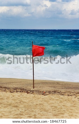 Red flag on beach with stormy weather