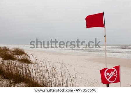 Red flags on a Gulf Coast Beach signal swimming in ocean prohibited due to dangerous surf, undercurrent and storm conditions