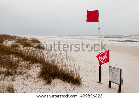 Red flags on a Gulf Coast Beach signal Water closed to public and prohibit swimming in ocean due to dangerous surf, undercurrent and storm conditions