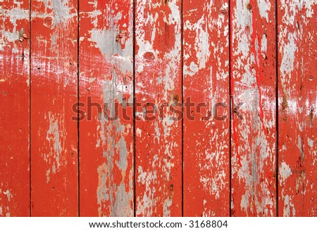 Red flaky paint on a wooden fence. - stock photo