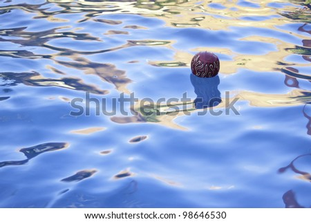 red flame ball floating in pool in summer time - stock photo