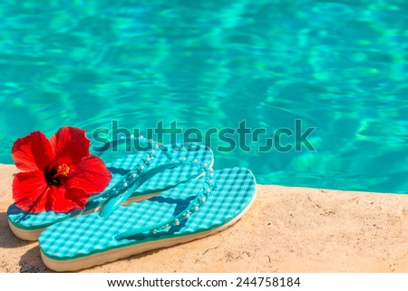 red flower and flip flops at the edge of the pool - stock photo