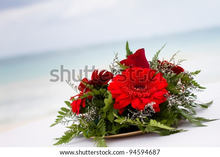 Red Flowers at the Beach placed for a wedding in Tulum Mexico - stock photo