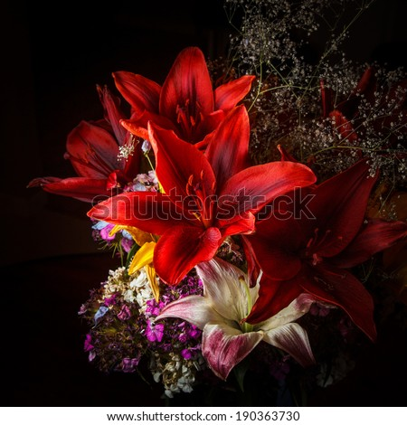 Red flowers - day lilies, baby's breath, and other purple flowers in an arrangement against a dark background.  Photographed with flash to create some mood and keep the focus on the flowers. - stock photo