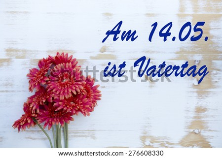 red flowers on wood with german text: Am 14.05. ist Vatertag (fathers day on 14.04.) - stock photo