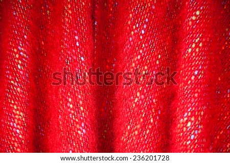 Red fluffy wool material with colorful embroidery.