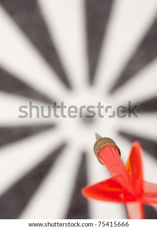 Red flying dart to dartboard bull's eye - stock photo