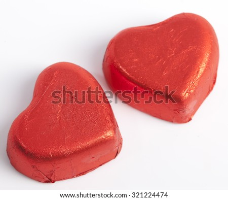 Red Foil wrapped chocolate hearts - stock photo