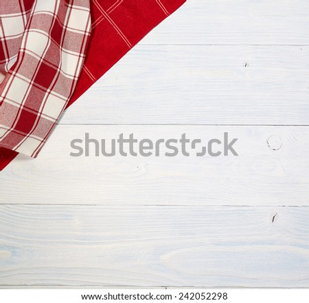 red folded tablecloth over old wooden table  - stock photo