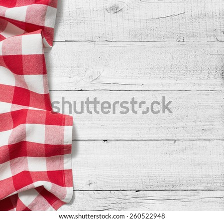red folded tablecloth over white wooden table - stock photo