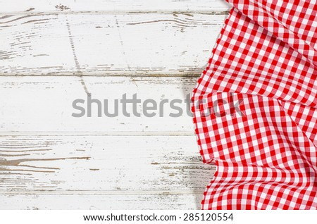 Red folded tablecloth over wooden table - stock photo