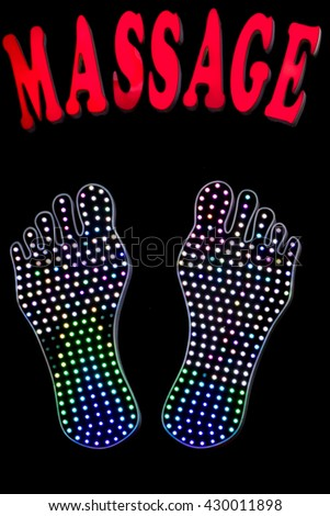 Red foot massage neon sign on black background with illuminated feet design in Saigon. Vietnam