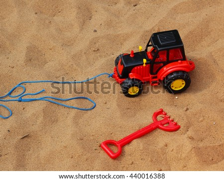 Red fork beach toy and excavator - stock photo