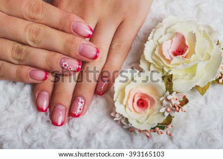 Red french nail art with flower on white textile