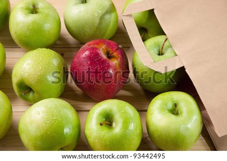 Red fresh apple lying on wooden boards among green ones