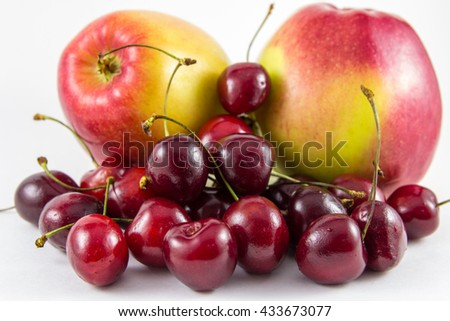 Red fresh cherries and apples isolated on white background