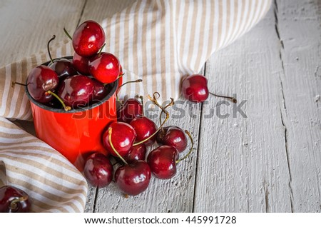 Red fresh cherries on old wooden table