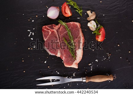 Red fresh raw fillet of T-Bone steak cut seasoning salt pepper and rosemary with fork on black background. - stock photo
