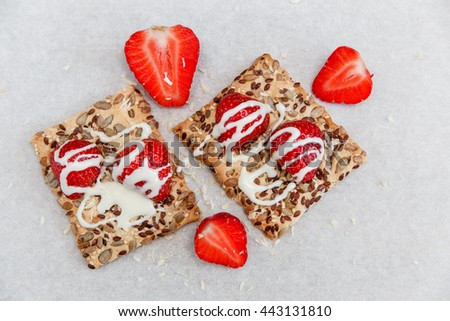 Red Fresh Strawberries are on the Cracker with Grains,Sweet Milk  on the White Paper.Breakfast Organic Healthy Tasty Food.Cooking Vitamins Ingredients.Summer Fruits.Top View - stock photo