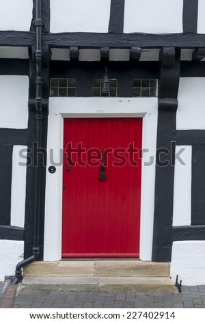 Red front door in a traditional English timber framed Tudor house - stock photo