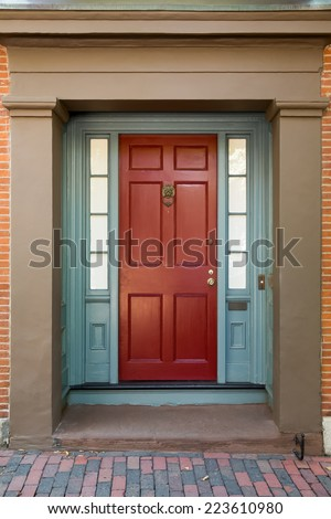 Red Front Door with Blue Door Frame and Windows on Tan Building on Brick Street