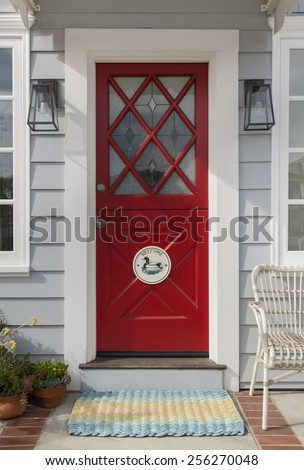 Red Front Door with Ornate Diamond Cross Hatch Window Panes and Welcome Decoration - stock photo