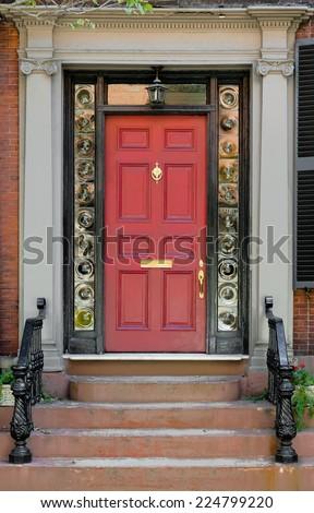 Red Front Door with Surrounding Black Door Frame and Bulls Eye Glass - stock photo