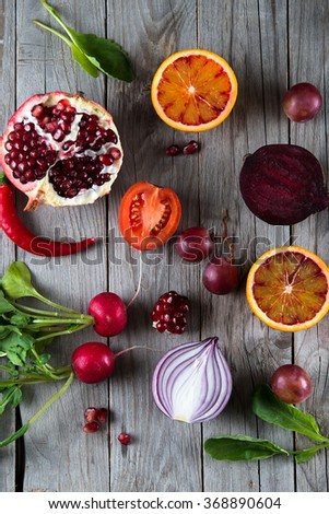 Red fruits and vegetables on wooden background - stock photo