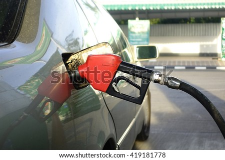 Red Fuel nozzle,Refueling the Car at a Gas Station:Close up,select focus with shallow depth of field. - stock photo