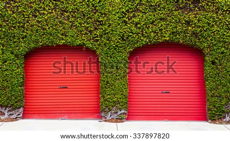 red garage doors over green leaves - stock photo