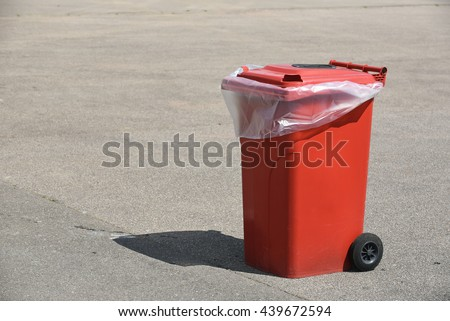 Red garbage collector at an asphalt square prepared for an event