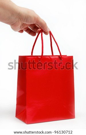 Red gift bag in the women's hand on a white background.