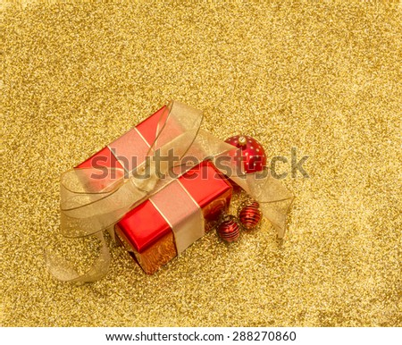 Red gift box and baubles with gold ribbon on a gold glitter background with copy space - stock photo