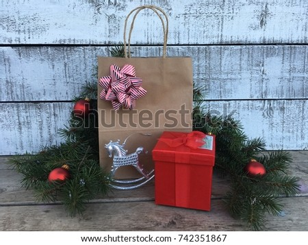 Red gift box and paper gift bag with greenery and ornaments against a white washed wall