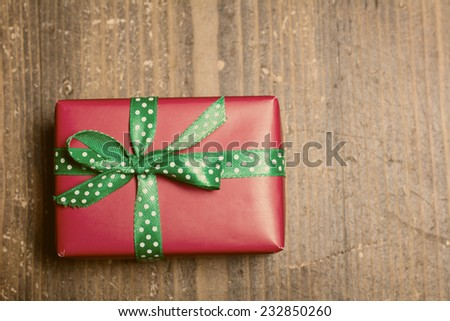 Red gift box lies on a wooden background. Vintage color