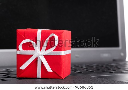 red gift box on a laptop keyboard - stock photo
